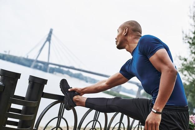 Retrato da vista lateral de um homem africano esportivo que está esticando as pernas