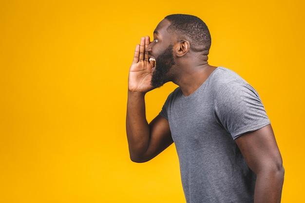 Retrato da vista lateral de um homem afro-americano novo que grita em voz alta com a mão em sua boca isolada na parede amarela.