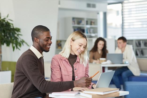 Retrato da vista lateral de um homem afro-americano sorridente com uma aluna usando o laptop na biblioteca da faculdade e gostando de estudar.