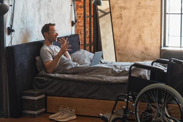 Retrato da vista lateral de um homem moderno com deficiência falando ao smartphone na cama, cadeira de rodas em primeiro plano, espaço de cópia