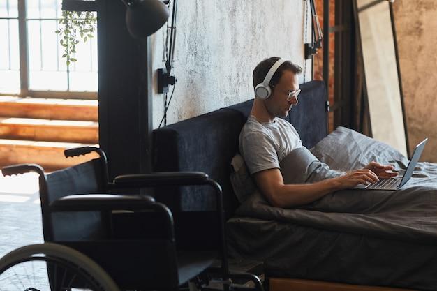 Retrato da vista lateral de um homem moderno com deficiência usando o laptop na cama, a cadeira de rodas em primeiro plano, copie o espaço
