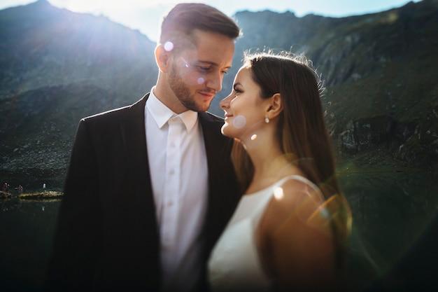 Retrato da vista lateral de um incrível noivo e noiva olhando um para o outro sorrindo, abraçando-se contra o nascer do sol nas montanhas.