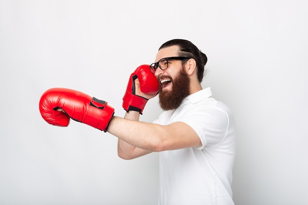Retrato da vista lateral de um jovem barbudo em uma camiseta branca socando com luvas de boxe vermelhas
