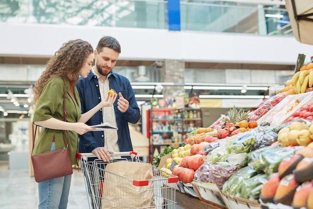 Retrato da vista lateral de um jovem casal moderno escolhendo vegetais enquanto faz compras no mercado de fazendeiros