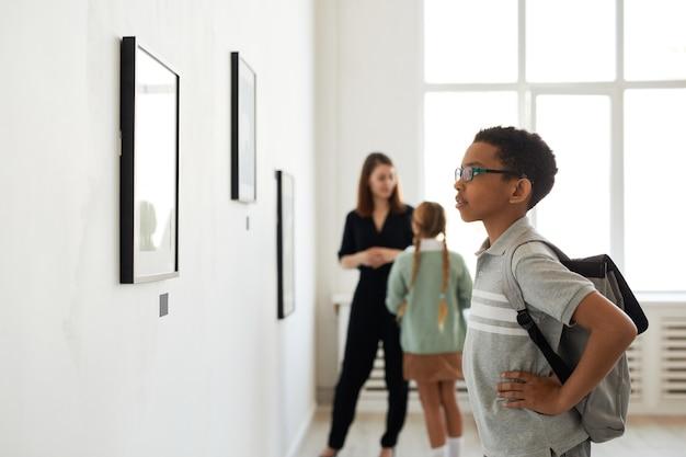 Retrato da vista lateral de um jovem estudante afro-americano olhando pinturas na galeria de arte moderna, copie o espaço