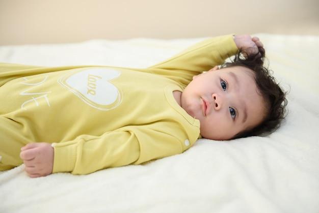 Retrato da vista lateral de um lindo bebezinho asiático deitado no lençol branco, olhe para a câmera