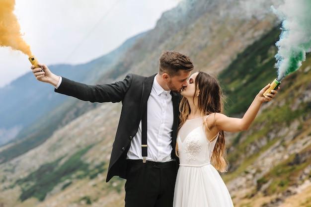 Retrato da vista lateral de um lindo casal se beijando nas montanhas, segurando granadas de fumar.