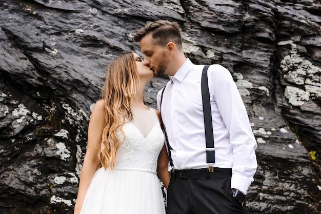 Retrato da vista lateral de um lindo jovem noivo e noiva beijando contra uma rocha negra nas montanhas.