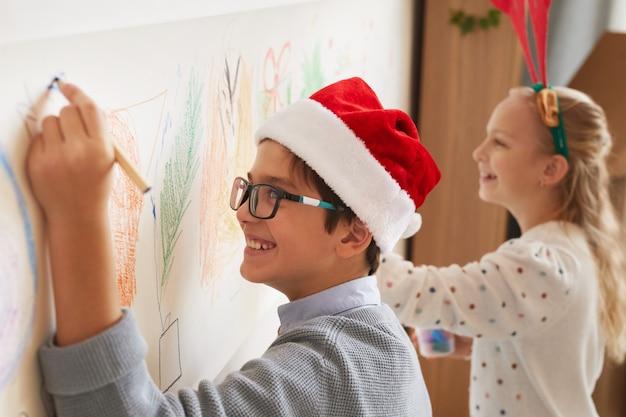 Retrato da vista lateral de um menino e uma menina desenhando nas paredes enquanto usava gorros de papai noel no natal, copie o espaço
