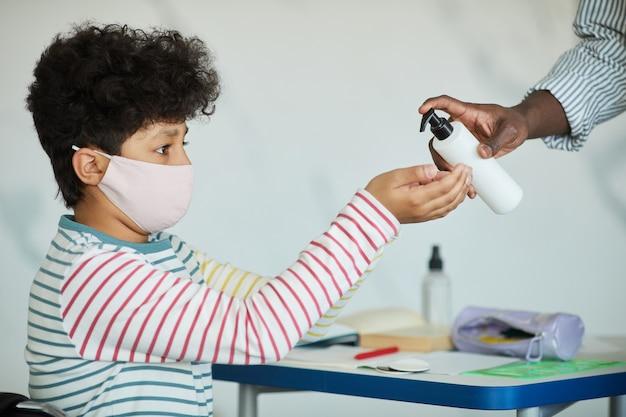 Retrato da vista lateral de um menino usando máscara e higienizando as mãos na sala de aula da escola, medidas de segurança ambiciosas, copie o espaço
