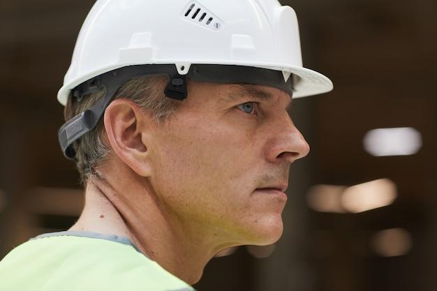 Retrato da vista lateral de um trabalhador da construção civil profissional usando capacete e olhando para longe,