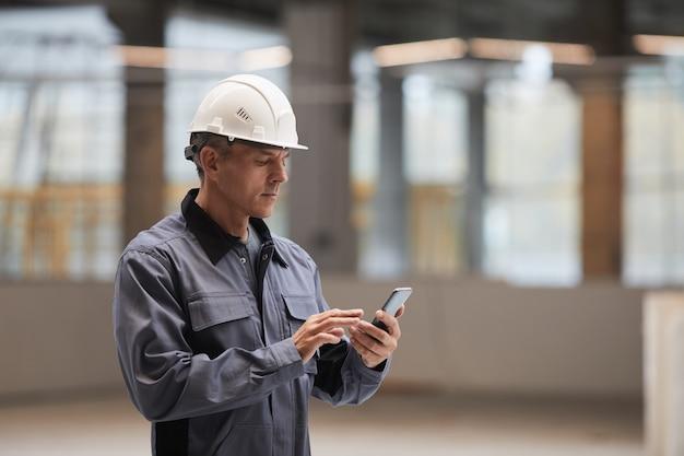 Retrato da vista lateral de um trabalhador maduro usando o smartphone em pé no canteiro de obras ou em uma oficina industrial,