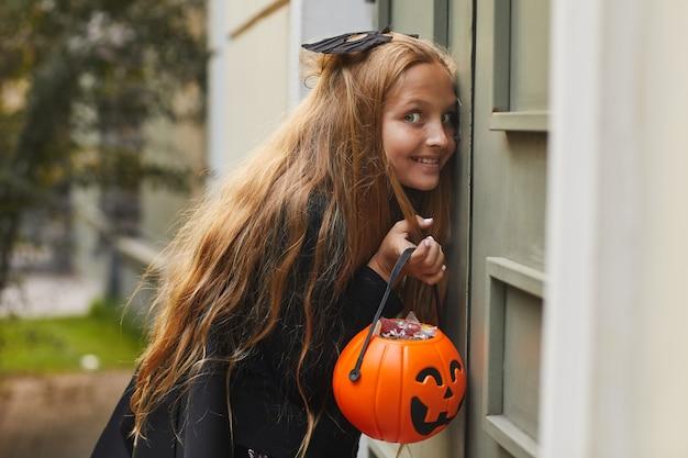 Retrato da vista lateral de uma adolescente travessa ouvindo na porta enquanto brinca de esconde-esconde ou travessura ou travessura no halloween