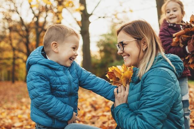 Retrato da vista lateral de uma adorável jovem mãe brincando com seus filhos enquanto seu filho está dando a ela um buquê de folhas sorrindo ao ar livre.