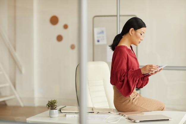 Retrato da vista lateral de uma elegante empresária asiática sentada na mesa e usando o tablet digital em um escritório branco moderno, copie o espaço