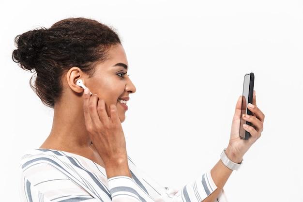 Retrato da vista lateral de uma jovem africana atraente carregando uma mochila em pé, isolada na parede branca, ouvindo música com fones de ouvido sem fio, segurando o telefone celular, selfie