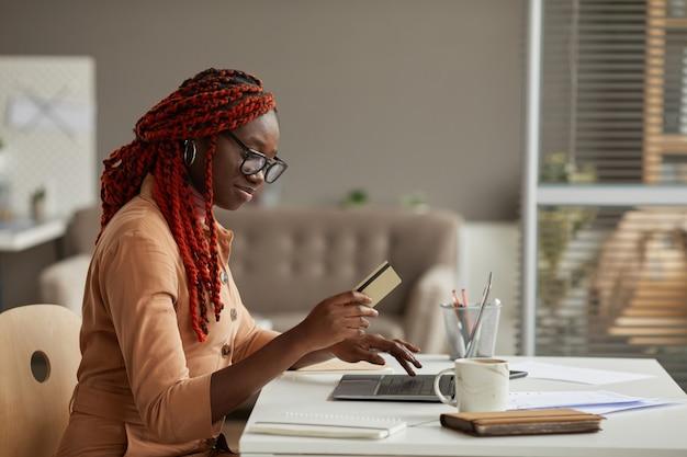 Retrato da vista lateral de uma jovem afro-americana segurando um cartão de crédito enquanto faz compras online no escritório em casa, copie o espaço