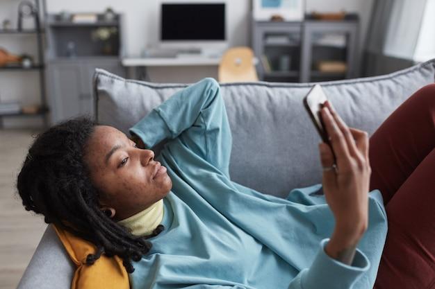 Retrato da vista lateral de uma jovem afro-americana segurando um smartphone enquanto estava deitada no sofá em casa com foco nas imperfeições reais da pele