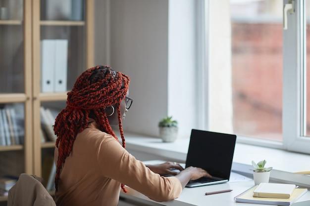 Retrato da vista lateral de uma jovem afro-americana usando o laptop enquanto estuda ou trabalha em casa pela janela, copie o espaço