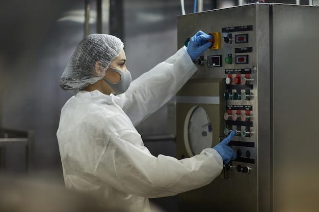 Retrato da vista lateral de uma jovem apertando os botões do painel de controle enquanto opera unidades da máquina na fábrica de alimentos, copie o espaço