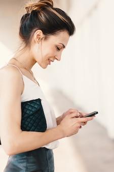 Retrato da vista lateral de uma jovem elegante sorridente usando um telefone inteligente