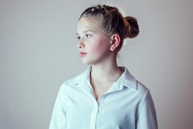 Retrato da vista lateral de uma jovem loira com o cabelo preso em um coque, vestindo uma camisa branca