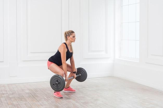 Retrato da vista lateral de uma jovem mulher atlética bonita fisiculturista em shorts rosa e blusa preta, fazendo agachamentos e se exercitando na academia com a barra na parede branca. indoor, studio shot,