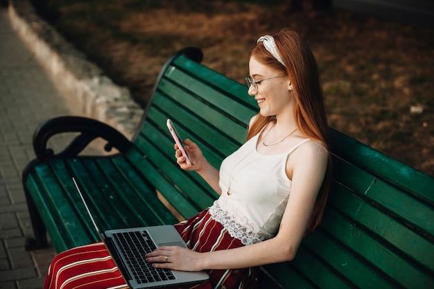 Retrato da vista lateral de uma jovem mulher bonita olhando para um smartphone com um laptop nas pernas. influenciador feminino com cabelo ruivo e sardas, sentado em um banco.