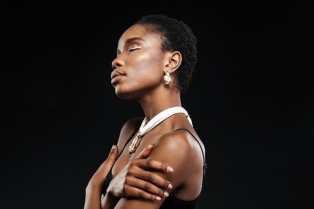 Retrato da vista lateral de uma jovem mulher étnica bonita isolada na parede preta