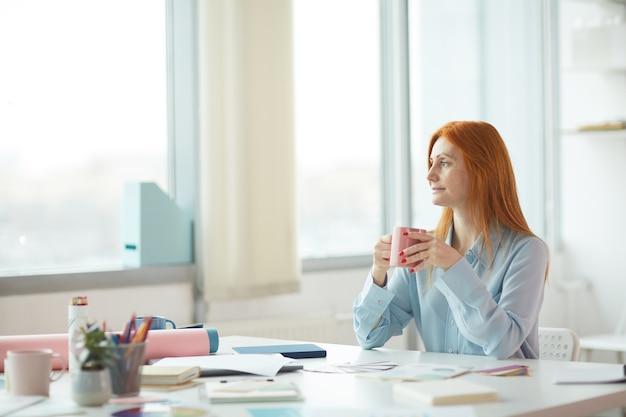 Retrato da vista lateral de uma jovem sardenta sonhando acordada em um escritório moderno enquanto bebe café no local de trabalho, copie o espaço