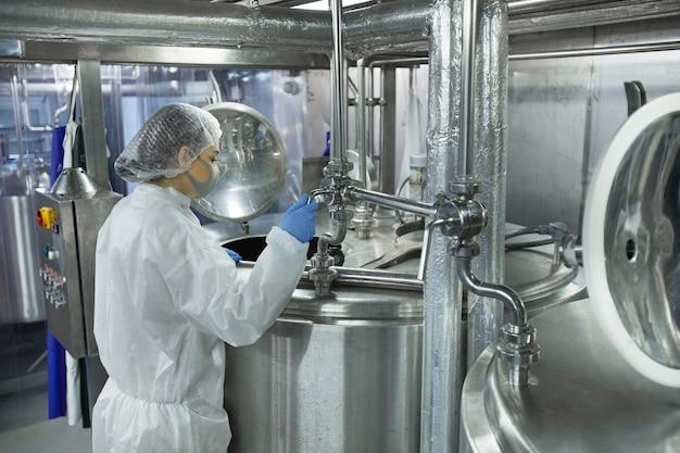 Retrato da vista lateral de uma jovem usando máscara e roupas protetoras enquanto trabalhava em uma fábrica de alimentos, copie o espaço