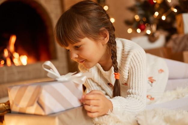Retrato da vista lateral de uma linda criança do sexo feminino com suéter branco e chapéu de papai noel, posando na sala festiva com lareira e árvore de natal, jogando perto de caixas de presentes de ano novo.