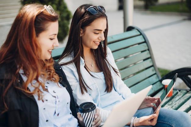 Retrato da vista lateral de uma linda mulher de cabelos compridos, sentada em um banco com a amiga, olhando para um tablet sorrindo.