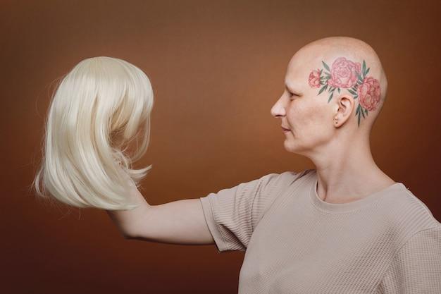Retrato da vista lateral de uma mulher careca confiante segurando uma peruca de cabelo loiro contra um fundo marrom no estúdio.