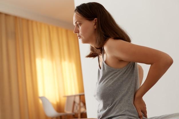Retrato da vista lateral de uma mulher doente, com roupas casuais, sentada na cama, tocando suas costas, sofrendo de dores nos rins, tendo problemas de saúde, precisa de tratamento.