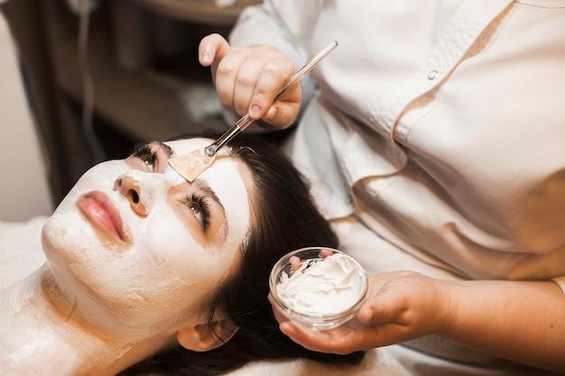 Retrato da vista lateral de uma mulher encantadora, tendo uma máscara branca de cuidados da pele aplicada no rosto, olhando para cima em um centro de spa.