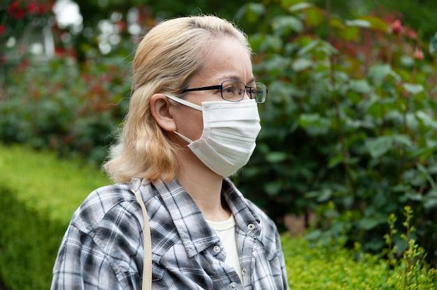 Retrato da vista lateral de uma mulher loira de meia-idade com óculos usando máscara cirúrgica branca. proteção contra coronavírus (covid-19)