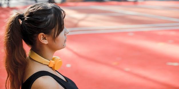 Retrato da vista lateral de uma mulher plus size fazendo exercícios para perder peso em um parque esportivo pela manhã.