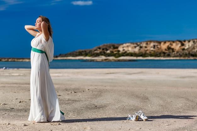Retrato da vista lateral de uma mulher relaxando respirando ar fresco na praia