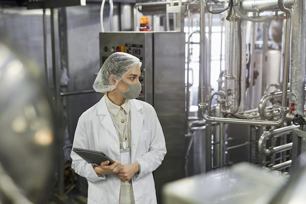 Retrato da vista lateral de uma trabalhadora usando máscara e segurando um tablet digital durante a inspeção de controle de qualidade na fábrica de alimentos, copie o espaço