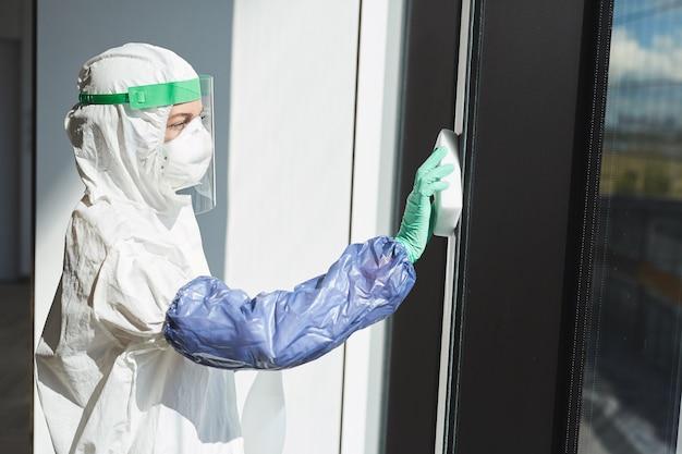 Retrato da vista lateral de uma trabalhadora vestindo um traje anti-risco, desinfetando janelas em um prédio comercial,