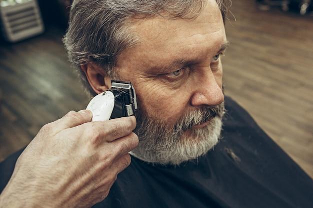Retrato da vista lateral do close-up do homem caucasiano barbudo sênior considerável que obtém a barba que prepara na barbearia moderna.