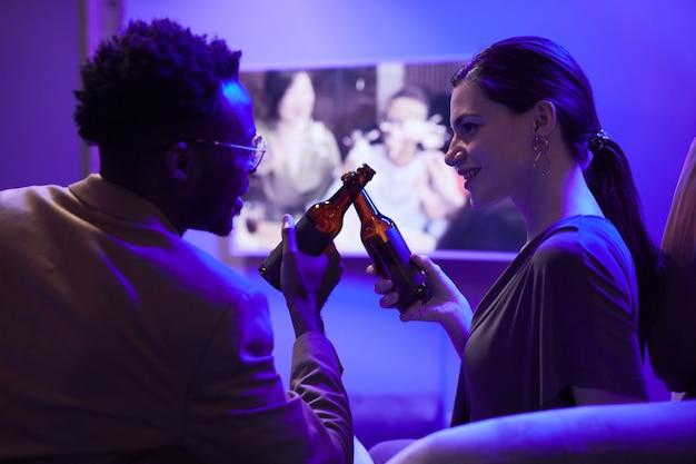 Retrato da vista lateral do cupê bebendo cerveja enquanto aproveita a festa em casa