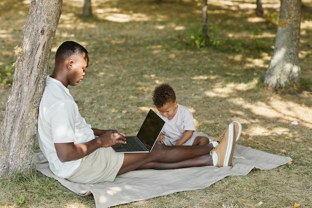Retrato da vista lateral do pai afro-americano usando o laptop enquanto brincava com o filho bonito no parque cópia s.