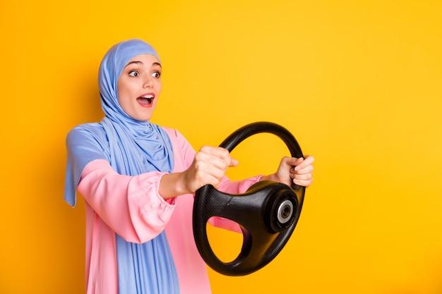 Retrato da vista lateral do perfil de muslimah muito atento espantado e alegre usando um hijab dirigindo um carro invisível com brilho de fundo amarelo