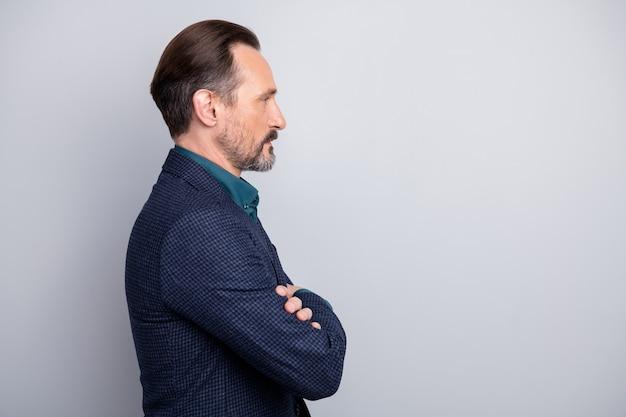 Retrato da vista lateral do perfil de um homem maduro em trajes formais com os braços cruzados