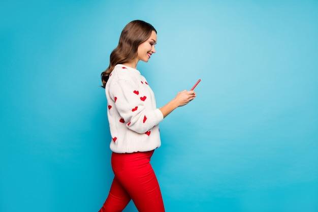 Retrato da vista lateral do perfil de uma bela garota atraente adorável alegre usando o gadget de envio de mensagem sms e o tempo livre