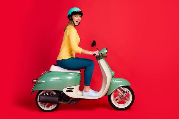 Retrato da vista lateral do perfil de uma garota alegre andando de motocicleta com a boca aberta na parede vermelha