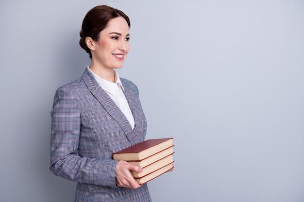 Retrato da vista lateral do perfil dela ela atraente qualificado intelectual alegre bibliotecário vestindo blazer xadrez casual segurando a cópia do livro, espaço em branco vazio isolado fundo cinza cor pastel