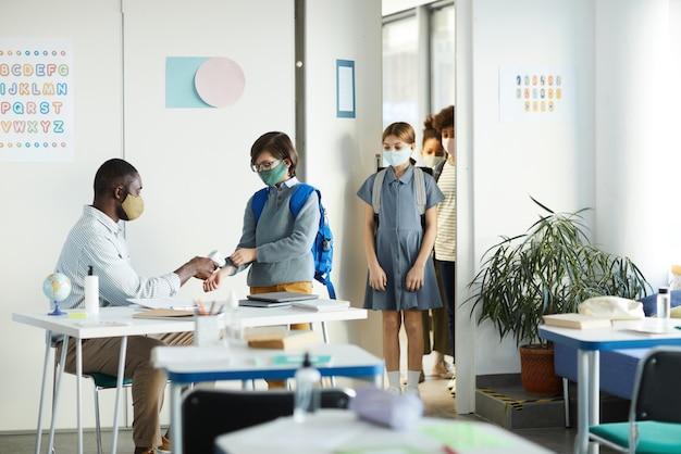 Retrato da vista lateral do professor verificando a temperatura das crianças entrando na sala de aula na escola, segurança ambiciosa